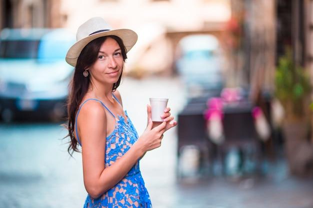 Donna a roma con caffè per andare in vacanza. ragazza caucasica felice sorridente divertendosi ridendo sul caffè italiano marciapiede durante le vacanze a roma, italia, europa.