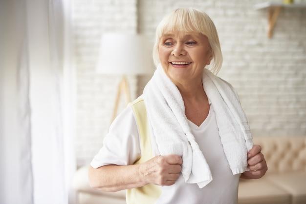 Donna abbastanza anziana allegra dopo l'allenamento di mattina.
