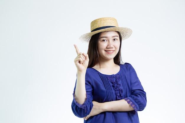 Donna abbastanza asiatica che indossa una fine del ritratto del cappello su su bianco con copyspace.