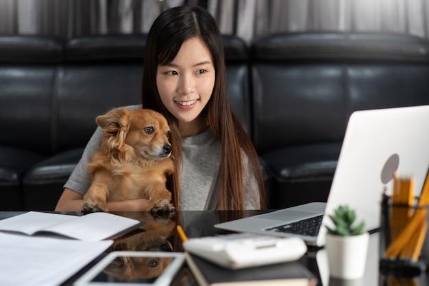 Donna abbastanza asiatica che lavora a distanza dalla casa facendo uso del computer portatile che si siede sullo strato o sul sofà in salone per lavoro online con il cane e il guardiano svegli del cucciolo dell'animale domestico, concetto dell'equilibrio di vita del lavoro.