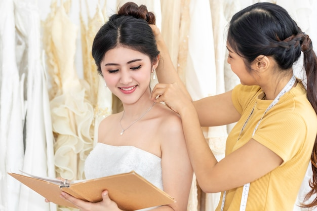 Donna abbastanza asiatica che sceglie vestito in un negozio con l'assistente del sarto.