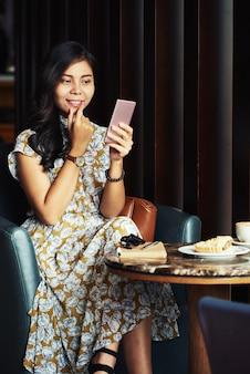 Donna abbastanza asiatica che si siede in caffè e che prende selfie con lo smartphone
