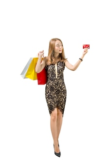 Donna abbastanza asiatica con i sacchetti della spesa che mostrano la sua carta di credito