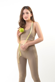 Donna abbastanza asiatica con la mela e nastro adesivo di misura su bianco