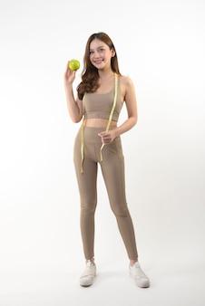 Donna abbastanza asiatica con la mela e nastro adesivo di misura