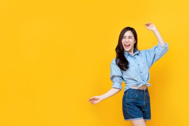 Donna abbastanza asiatica emozionante che sorride con l'aumento del braccio