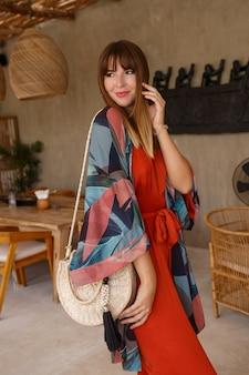 Donna abbastanza bianca in elegante estate bohemain autfit in posa in un caffè tropicale.
