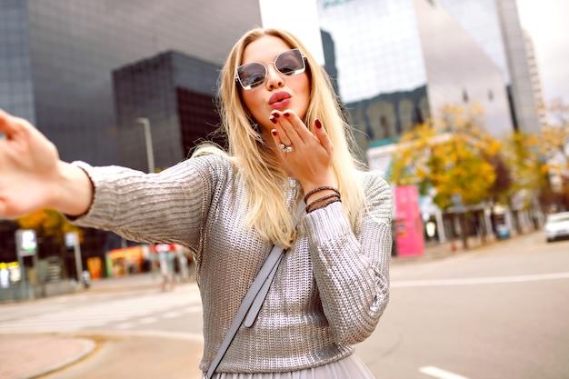 Donna abbastanza bionda che fa selfie in strada vicino alla zona degli edifici moderni, indossa un maglione grigio e accessori glamour, invia un bacio d'aria, umore romantico, donna turistica felice, tempo di primavera autunnale.