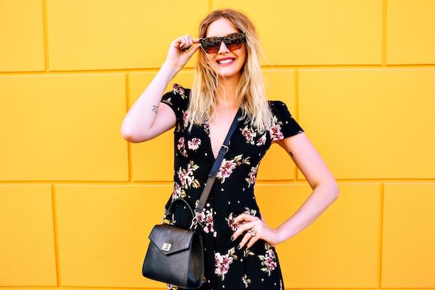 Donna abbastanza bionda che indossa un abito floreale, in posa vicino alla parete gialla