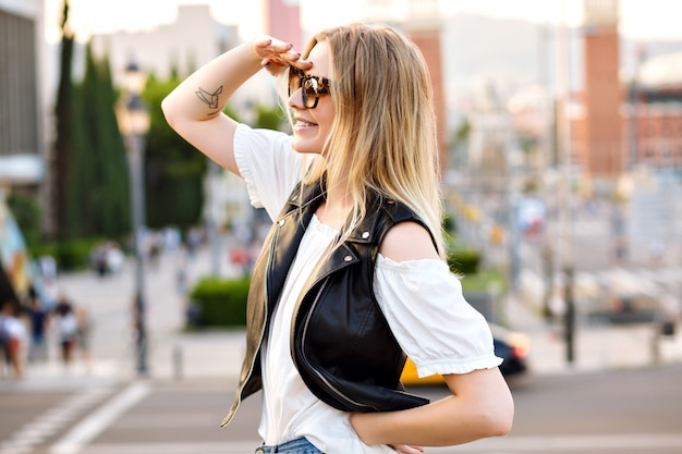 Donna abbastanza bionda che posa alla bella strada europea, indossando occhiali da sole e abbigliamento casual