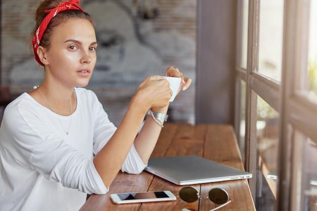 Donna abbastanza bionda che si siede nella caffetteria