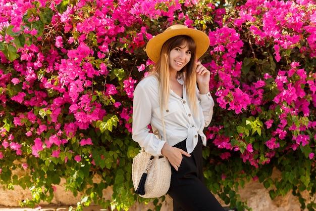 Donna abbastanza bionda in cappello di paglia che posa sopra l'albero di fioritura rosa nel giorno di molla soleggiato