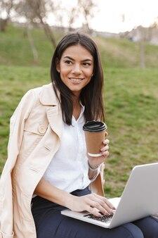 Donna abbastanza giovane che per mezzo del computer portatile