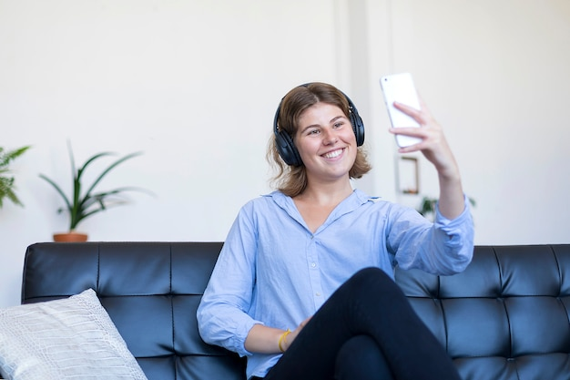 Donna abbastanza giovane dei capelli lunghi che si siede su un divano che fa selfie sul suo telefono