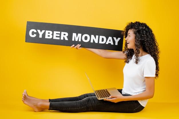 Donna abbastanza giovane dell'africano nero che si siede con il computer portatile e il segno cyber di lunedì isolato sopra il giallo