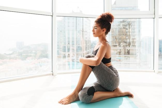Donna abbastanza in buona salute che fa esercizio difficile sul pavimento