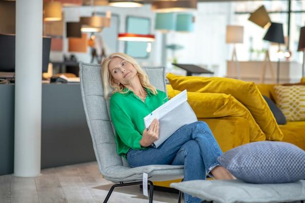 Donna abbastanza pensierosa con campioni di tessuto tra le mani, mezzo disteso su una sedia morbida in un negozio di mobili, guardando di lato.