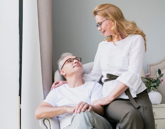 Donna abbastanza senior che esamina uomo su un sofà