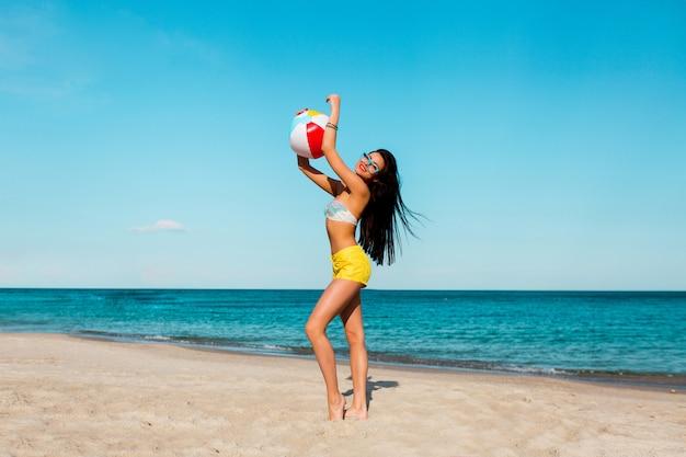 Donna abbronzata allegra abbastanza sexy che gioca palla sulla spiaggia di estate. indossa camicie gialle, top colorato e occhiali fantastici.