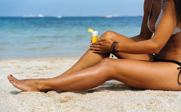 Donna abbronzata che applica protezione solare nelle sue gambe abbronzate in una spiaggia paradisiaca