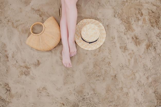 Donna abbronzata gambe, cappello di paglia e borsa sulla spiaggia di sabbia. rilassarsi in spiaggia, con i piedi sulla sabbia.