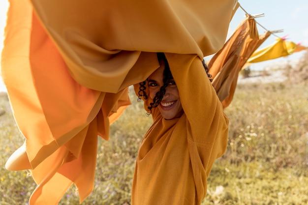Donna accanto a stendibiancheria nei campi