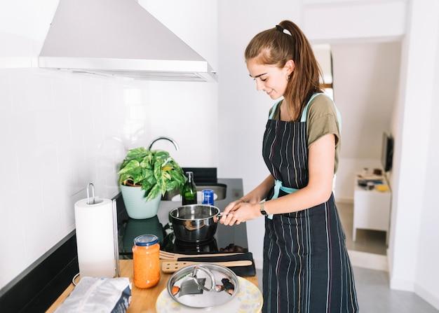 Donna acqua bollente nella casseruola sopra la cucina elettrica
