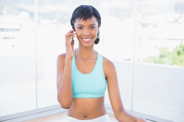 Donna adatta affascinante che chiama qualcuno con il suo telefono cellulare