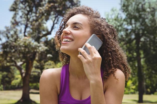 Donna adatta al telefono nel parco