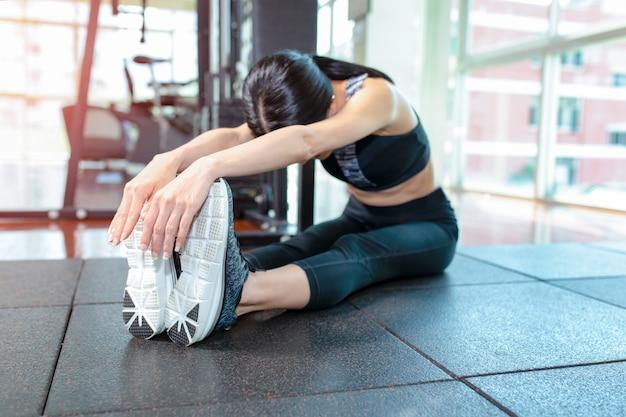 Donna adatta che allunga la sua gamba per riscaldarsi in palestra