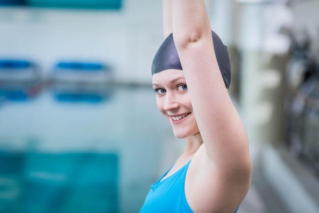 Donna adatta che alza le braccia in piscina