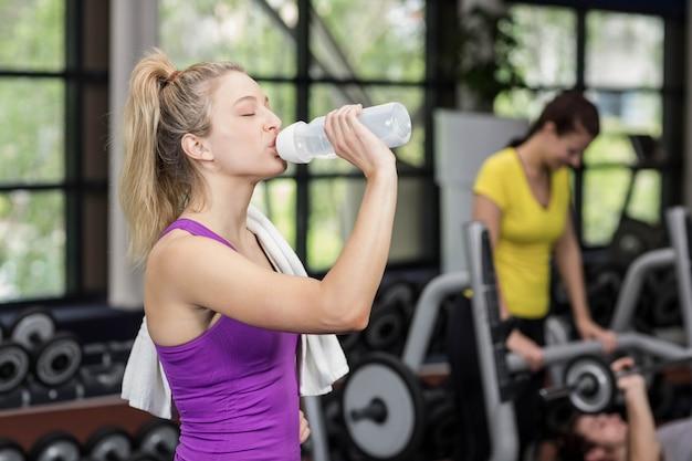 Donna adatta che beve dalla bottiglia di acqua in palestra