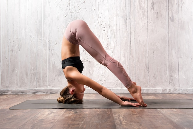 Donna adatta che esercita posa di yoga di sirsasana