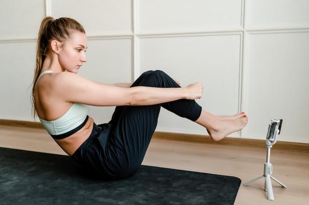 Donna adatta che fa allenamento di sport a casa con addestramento online