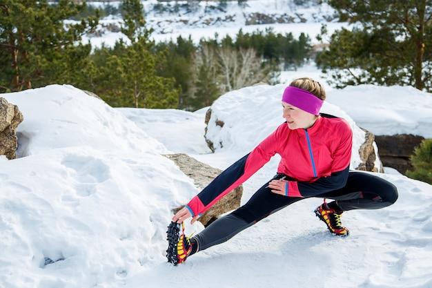 Donna adatta che fa allungando le esercitazioni prima di correre all'aperto