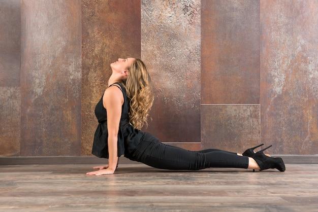 Donna adatta che fa posa di yoga di bhujanasana