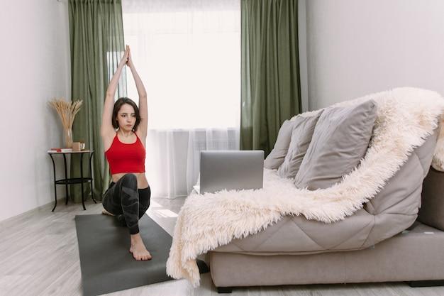 Donna adatta che fa yoga e che guarda i tutorial online sul computer portatile