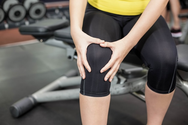 Donna adatta che ha dolore delle ginocchia alla palestra