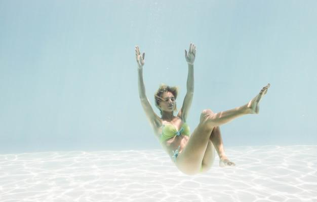 Donna adatta che nuota sotto l'acqua in piscina