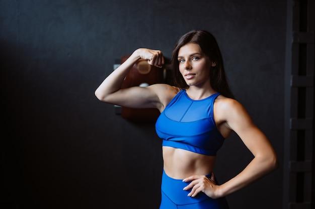 Donna adatta che posa sulla macchina fotografica. personal trainer che mostra la sua forma. bellezza dello sport moderno.