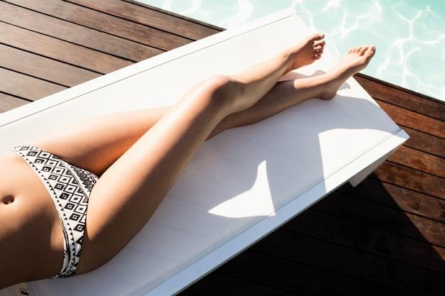 Donna adatta che si trova sulla sedia a sdraio a bordo piscina