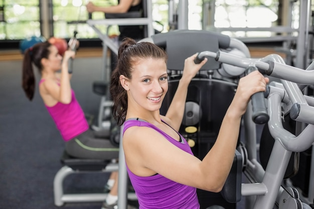 Donna adatta che utilizza la macchina del peso in palestra
