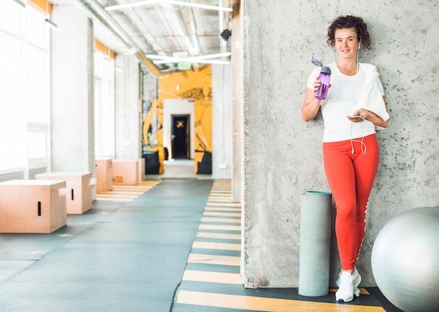 Donna adatta con la bottiglia di acqua e cellulare che si appoggia parete in palestra