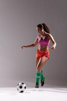 Donna adatta con pallone da calcio