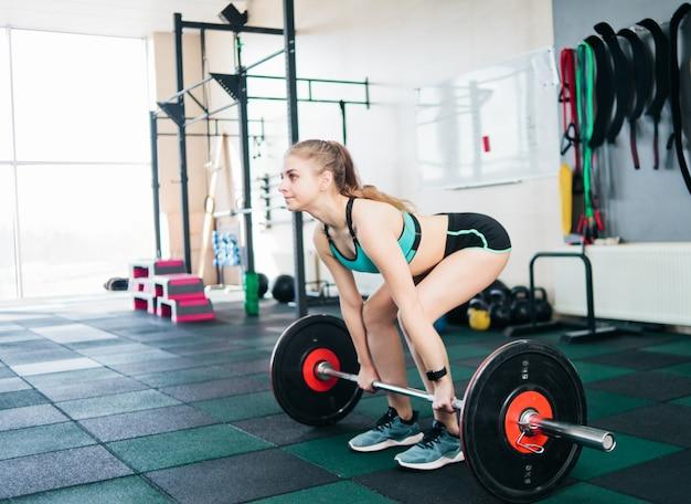 Donna adatta dei giovani che fa deadlift con un bilanciere in palestra. allenamento con i pesi gratuito