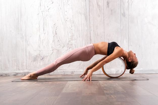 Donna adatta dei giovani che fa posa di yoga di purvottanasana