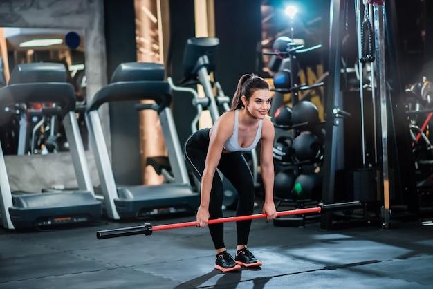 Donna adatta dei giovani che si esercita con la barra di allenamento ponderata nella palestra