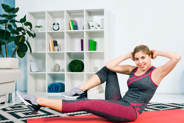 Donna adatta dei giovani che si esercita in una palestra che si trova sulla stuoia che fa gli esercizi di innalzamento e di torsione della gamba