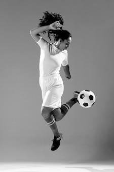 Donna adatta del colpo pieno che gioca con il pallone da calcio