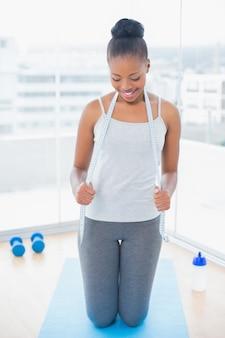 Donna adatta in abbigliamento sportivo che tiene nastro di misurazione intorno al collo